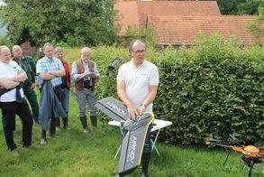 Dirk Schmidt erklärt die Funktion einer Drohne zum Überflug von Feldern